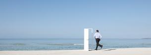 Man running on beach towards open door, rear viewの写真素材 [FYI04321774]