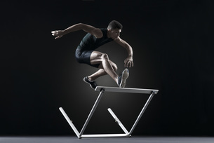 Male athlete clearing hurdleの写真素材 [FYI04321784]