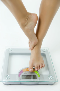 Woman standing on one leg on bathroom scale, low sectionの写真素材 [FYI04321794]