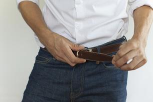 Man fastening belt, mid sectionの写真素材 [FYI04321796]