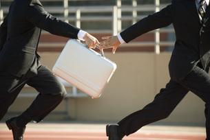 Businessmen running in relay race, handing off briefcaseの写真素材 [FYI04321828]