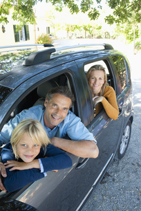 Family together in car, leaning out windows and smiling at cの写真素材 [FYI04321833]
