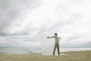 Man trapped in plastic on beachの写真素材 [FYI04321834]