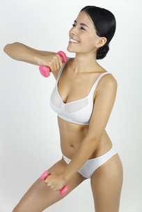 Woman in underwear lifting dumbbellsの写真素材 [FYI04321844]