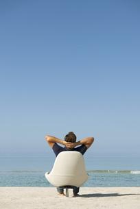 Man sitting in armchair on beach looking at ocean, rear viewの写真素材 [FYI04321847]