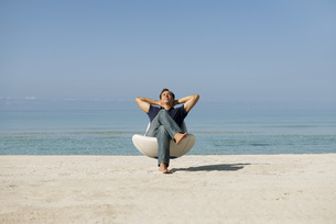 Mid-adult man relaxing in armchair on beach with eyes closedの写真素材 [FYI04321857]