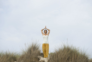 Mature woman doing sun salutation yoga poseの写真素材 [FYI04321862]