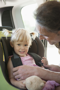 Father fastening little girl into car seatの写真素材 [FYI04321873]