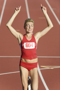 Woman running on track with arms raised in victoryの写真素材 [FYI04321874]