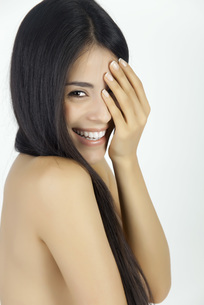 Woman covering one eye, smiling over shoulder at cameraの写真素材 [FYI04321876]