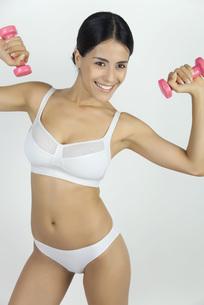 Woman in underwear lifting dumbbellsの写真素材 [FYI04321884]