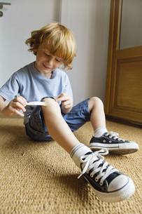 Boy removing adhesive bandage from kneeの写真素材 [FYI04321895]