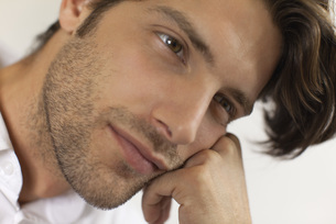 Man resting head on hand, daydreamingの写真素材 [FYI04321906]