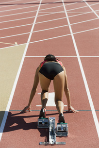 Woman crouched in starting position on running track, rear vの写真素材 [FYI04321910]