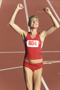 Woman running on track with arms raised in victoryの写真素材 [FYI04321913]