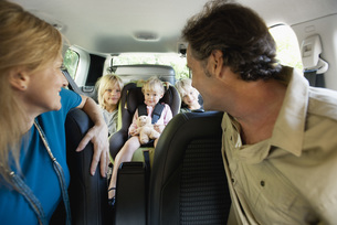 Family in car, parents looking over their shoulders at childの写真素材 [FYI04321940]