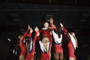 Team of female gymnasts celebrating victory togetherの写真素材 [FYI04321960]