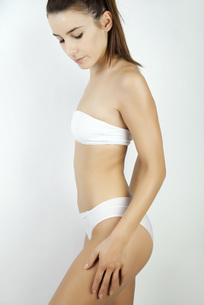 Young woman in underwear, looking down and touching thighの写真素材 [FYI04321965]