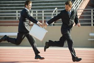 Businessmen handing off briefcase in relay raceの写真素材 [FYI04321997]