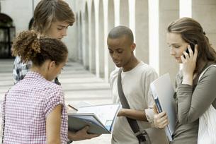 University students discussing schoolwork on campusの写真素材 [FYI04322020]
