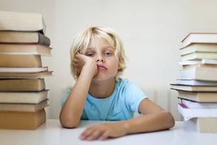 Boy sitting between two stacks of books with bored expressioの写真素材 [FYI04322022]