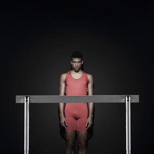 Male athlete standing behind hurdleの写真素材 [FYI04322035]