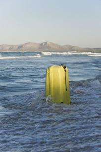 Wave breaking over suitcaseの写真素材 [FYI04322044]