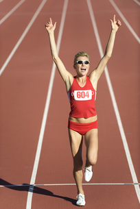Woman running on track with arms raised in victoryの写真素材 [FYI04322058]