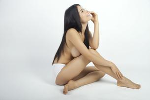 Woman sitting in underwear, daydreamingの写真素材 [FYI04322059]