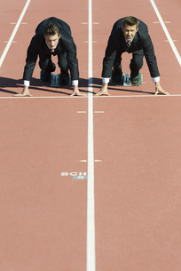 Businessmen crouched in starting position on running trackの写真素材 [FYI04322065]