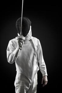 Fencer holding up foil, portraitの写真素材 [FYI04322078]