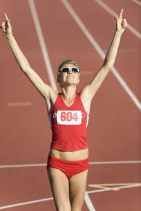Woman running on track with arms raised in victoryの写真素材 [FYI04322085]