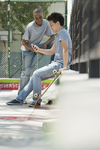 Young man using cell phone outdoors, friend watchingの写真素材 [FYI04322087]