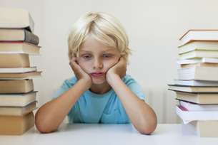 Boy sitting between two stacks of books, sulkingの写真素材 [FYI04322095]
