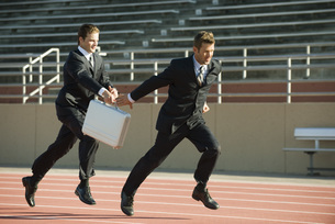 Businessmen running in relay race, handing off briefcaseの写真素材 [FYI04322117]