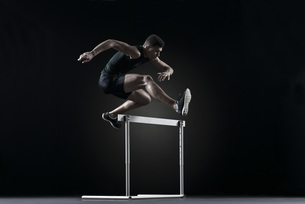 Male athlete clearing hurdleの写真素材 [FYI04322118]