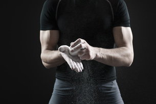 Male athlete applying chalk to hands, mid sectionの写真素材 [FYI04322128]