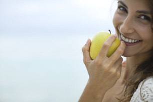 Woman eating apple, portraitの写真素材 [FYI04322134]