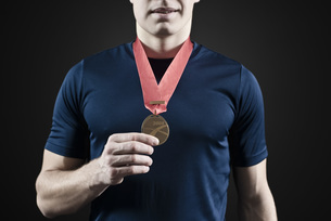 Male athlete holding medal, mid sectionの写真素材 [FYI04322141]