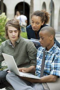 University students discussing homework on campus with laptoの写真素材 [FYI04322144]