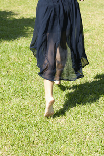 Woman barefoot in grass, rear viewの写真素材 [FYI04322167]