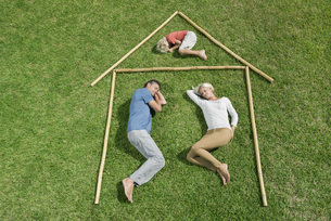 Family with one child lying on grass within outline of houseの写真素材 [FYI04322170]
