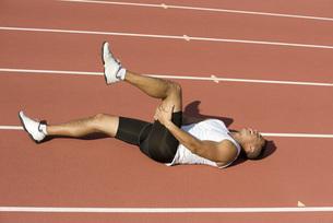 Injured runner lying on running trackの写真素材 [FYI04322190]
