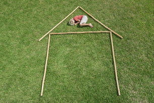 Boy lying on grass within outline of house, high angle viewの写真素材 [FYI04322192]