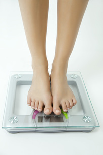 Woman weighing herself on bathroom scale, low sectionの写真素材 [FYI04322200]
