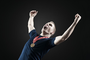 Male athlete shouting with arms raised in victoryの写真素材 [FYI04322202]
