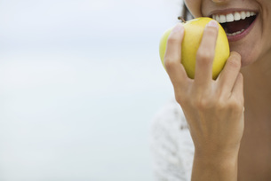 Woman eating apple, croppedの写真素材 [FYI04322218]