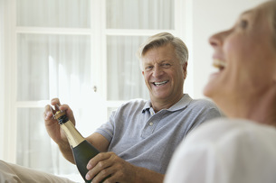 Couple relaxing together, man opening bottle of champagneの写真素材 [FYI04322225]