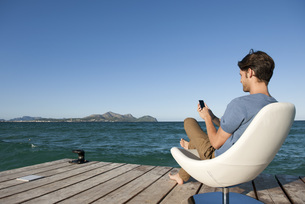 Young man sitting in armchair by lake using cell phone, sideの写真素材 [FYI04322246]