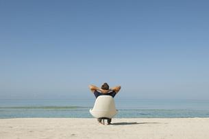 Man sitting in armchair on beach looking at ocean, rear viewの写真素材 [FYI04322306]